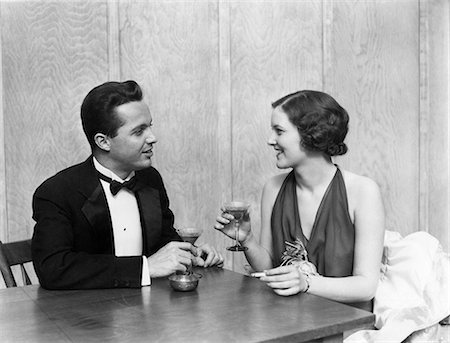 smoke - 1930s 1940s COUPLE DRINKING TOASTING CLUB TABLE SMOKING CIGARETTE MAN WOMAN MEN WOMEN COUPLES TUXEDO MARTINI RESTAURANT PARTY Stock Photo - Rights-Managed, Code: 846-08140035