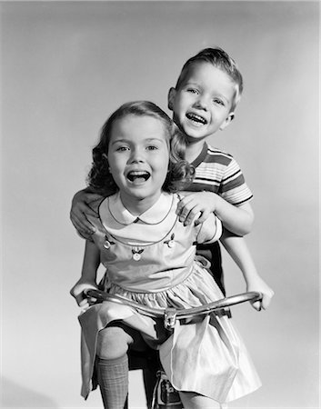 1950s GIRL WEARING A DRESS WITH  RIDING A TRICYCLE WHILE A BOY IS STANDING ON BACK HOLDING ON TO HER SHOULDERS Stock Photo - Rights-Managed, Code: 846-08140048