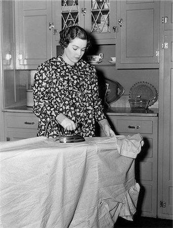 1930s 1940s WOMAN WEARING PRINTED SMOCK APRON STANDING IRONING BOARD PUSHING ELECTRIC IRON Stock Photo - Rights-Managed, Code: 846-08140042