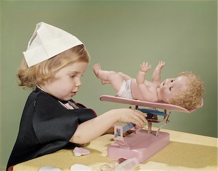 1960s LITTLE GIRL DRESSED IN NURSE'S COSTUME WEIGHING HER DOLL ON TOY BABY SCALE Stock Photo - Rights-Managed, Code: 846-08140059