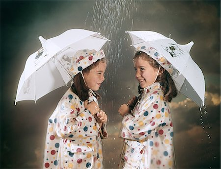 1960s SMILING TWIN GIRLS WEARING MATCHING POLKA DOT RAIN COATS AND HATS STANDING UNDER UMBRELLAS IN THE RAIN Stock Photo - Rights-Managed, Code: 846-08140064