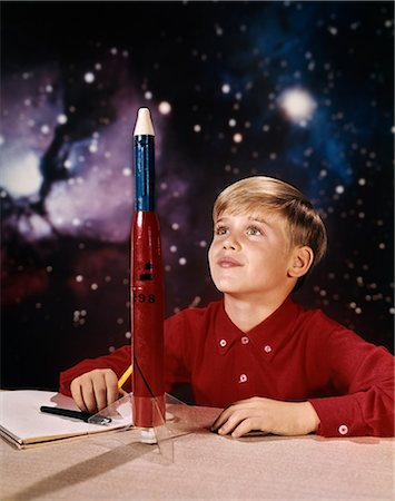 1960s BOY WITH MODEL ROCKET DAYDREAMING LOOKING AT ROCKET ON DESK STAR GALAXY BACKGROUND Stock Photo - Rights-Managed, Code: 846-08140065