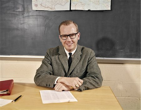 1960s SMILING MALE SCHOOL TEACHER SITTING AT DESK WEARING EYEGLASSES LOOKING AT CAMERA Stock Photo - Rights-Managed, Code: 846-08140076