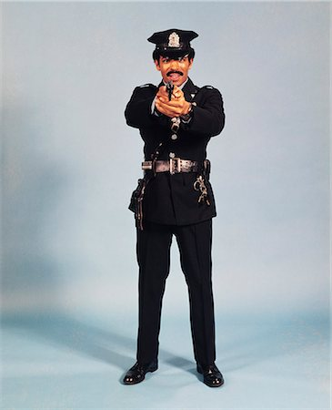 1970s FULL FIGURE STANDING AFRICAN AMERICAN MAN POLICEMAN OFFICER POINTING FIREARM AND LOOKING AT CAMERA Stock Photo - Rights-Managed, Code: 846-08140071