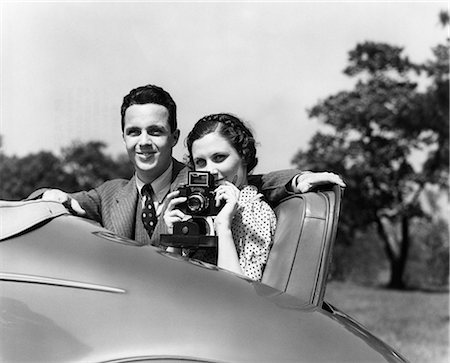 1930s COUPLE SITTING IN JUMP SEAT OF CAR POINTING CAMERA AT VIEWER Stock Photo - Rights-Managed, Code: 846-08140084