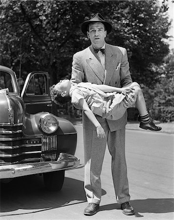 dangerous accident - 1950s DISTRAUGHT MAN LOOKING AT CAMERA CARRYING UNCONSCIOUS AND INJURED CHILD THAT WAS HIT BY A CAR Stock Photo - Rights-Managed, Code: 846-08140081