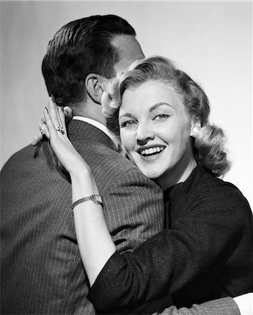 story - 1950s COUPLE ARM IN ARM EMBRACE HUG MAN FACE HIDDEN BY WOMAN SMILING  DISPLAYING NEW ENGAGEMENT DIAMOND RING ON HER FINGER Stock Photo - Rights-Managed, Code: 846-08140104