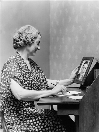 1930s 1940s SENIOR WOMAN SITTING AT DESK WRITING LETTER AS SHE HOLDS PICTURE PORTRAIT OF YOUNG MAN SON Stock Photo - Rights-Managed, Code: 846-08140109