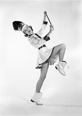 1960s WOMAN MAJORETTE BAND UNIFORM SHORT SKIRT BOOTS TASSELS MARCHING ONE LEG UP HOLDING BATON SMILING Stock Photo - Rights-Managed, Code: 846-08140101