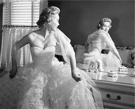 1950s BLONDE IN STRAPLESS GOWN WITH CRINOLINES TURNING TO LOOK AT BACK VIEW OF SELF IN MIRROR Stock Photo - Rights-Managed, Code: 846-08140111