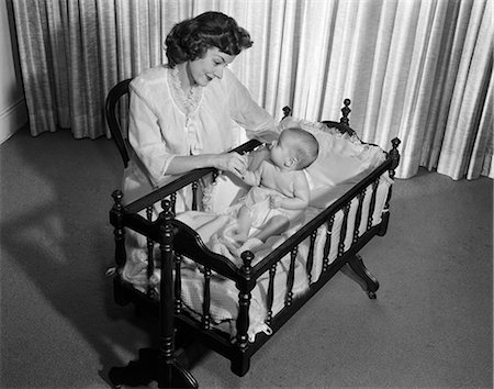 1950s SMILING WOMAN MOTHER KNEELING BY CRIB WITH BABY Stock Photo - Rights-Managed, Code: 846-08226057