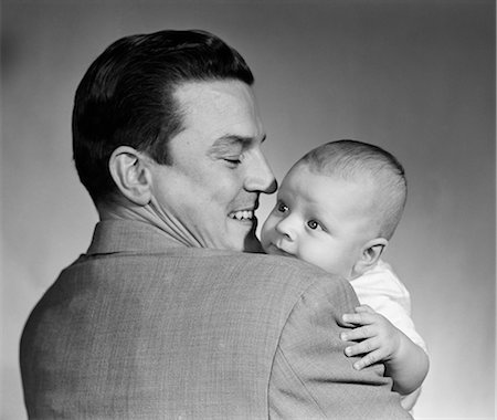 1950s PROUD SMILING MAN FATHER BACK TOWARD CAMERA HOLDING BABY SON FACE TO CAMERA Stock Photo - Rights-Managed, Code: 846-08226065