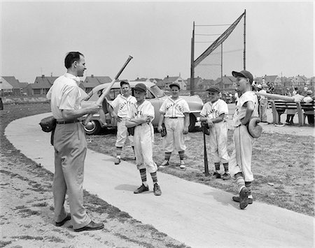1950s GROUP OF LITTLE LEAGUERS BASEBALL PLAYERS OFF OF FIELD RECEIVING INSTRUCTIONS FROM COACH HOLDING BAT & GLOVE Stock Photo - Rights-Managed, Code: 846-08226061