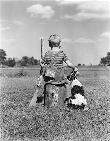 1940s BACK VIEW OF BOY WEARING HUNTING PERMIT HOLDING BB GUN SITTING ON TREE STUMP NEXT TO SPRINGER SPANIEL DOG Stock Photo - Rights-Managed, Code: 846-08226075