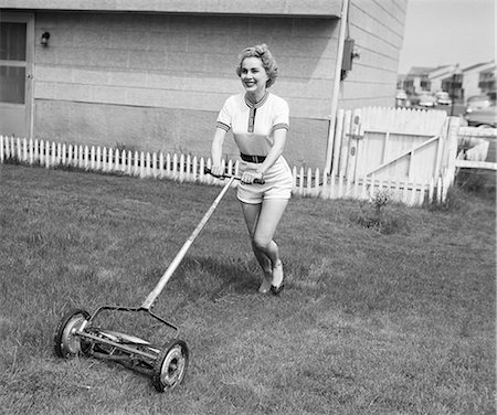1950s SMILING BLOND WOMAN IN SHORTS MOWING LAWN WITH PUSH MOWER Stock Photo - Rights-Managed, Code: 846-08226088