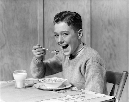 1930s 1940s SMILING BOY LOOKING AT CAMERA EATING BREAKFAST BOWL OF CEREAL AND GLASS OF MILK Stock Photo - Rights-Managed, Code: 846-08226081