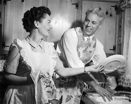 1950s SMILING HUSBAND IN APRON IN KITCHEN WASHING DISHES AS HAPPY WIFE DRIES Photographie de stock - Rights-Managed, Code: 846-08226097