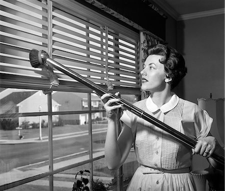 1950s WOMAN VACUUMING VENETIAN BLINDS ON WINDOW LOOKING OUT ONTO SUBURBAN STREET Stock Photo - Rights-Managed, Code: 846-08226099