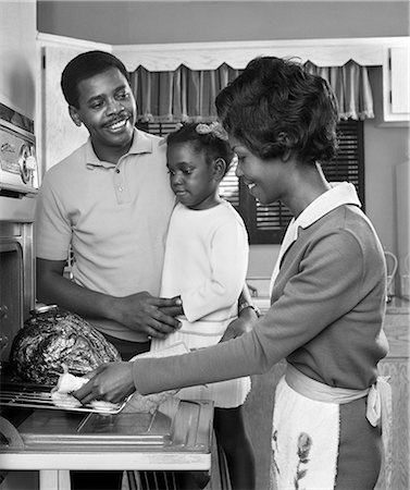 1960s AFRICAN AMERICAN FAMILY IN KITCHEN FATHER AND DAUGHTER WATCHING MOTHER REMOVE ROAST TURKEY FROM OVEN Stock Photo - Rights-Managed, Code: 846-08226105