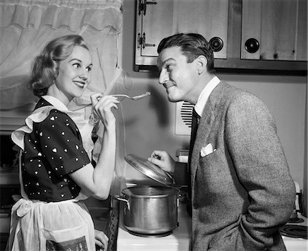 simsearch:846-02793283,k - 1950s SMILING HOUSEWIFE AT STOVE GIVING HAPPY HUSBAND TASTE OF HER COOKING Stock Photo - Rights-Managed, Code: 846-08226103