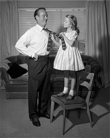 1950s CONFIDENT LITTLE GIRL STANDING ON CHAIR TYING NECKTIE FOR HER SMILING FATHER Stock Photo - Rights-Managed, Code: 846-08226113