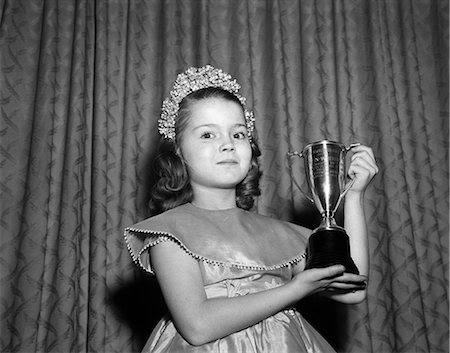 1950s 1960s YOUNG GIRL STANDING WITH TROPHY LOVING CUP WEARING TIARA PRETTY DRESS WINNER OF BEAUTY PAGEANT LOOKING AT CAMERA Stock Photo - Rights-Managed, Code: 846-08226124