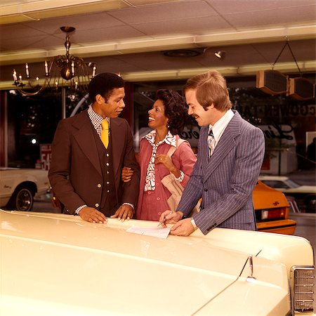 1970s MAN WOMAN AFRICAN AMERICAN COUPLE WITH DEALER SALESMAN IN AUTOMOBILE SHOWROOM BUYING NEW CAR Stock Photo - Rights-Managed, Code: 846-08226128