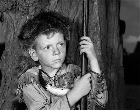 1950s BOY WEARING RACCOON SKIN HAT FRINGED WESTERN STYLE JACKET WITH POWDER HORN AND ANTIQUE RIFLE Stock Photo - Rights-Managed, Code: 846-08226120