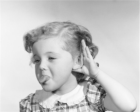 1950s LITTLE GIRL MAKING RUDE GESTURE STICKING OUT TONGUE CUPPING HAND ON EAR Stock Photo - Rights-Managed, Code: 846-08226121