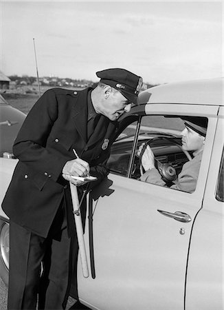 1950s POLICEMAN WITH STOPPED MOTORIST WRITING TICKET Stock Photo - Rights-Managed, Code: 846-08226136