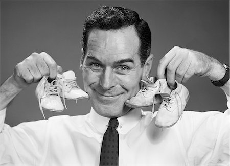 1950s SMILING PORTRAIT MAN HOLDING ONE PAIR OF BABY BOOTIES IN EACH HAND NEXT TO FACE Stock Photo - Rights-Managed, Code: 846-08226144