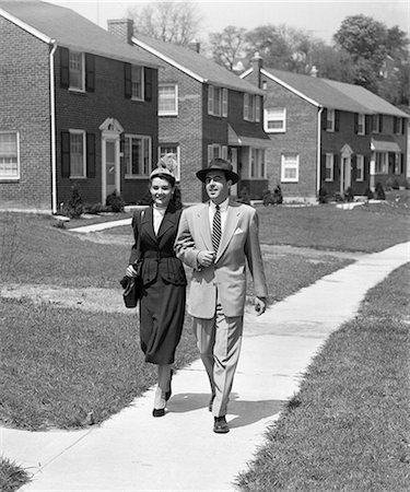 1950s MAN WOMAN COUPLE ARM IN ARM WALKING DOWN SUBURBAN SIDEWALK STREET OF NEWLY BUILT BRICK HOMES Stock Photo - Rights-Managed, Code: 846-08226140