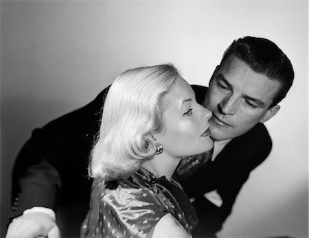 1950s 1960s COUPLE ALOOF WOMAN PRETTY BLONDE HAIR ELEGANT EARRINGS FASHION PROFILE ABOUT TO BE KISSED BY MAN STANDING BEHIND HER Stock Photo - Rights-Managed, Code: 846-08226154