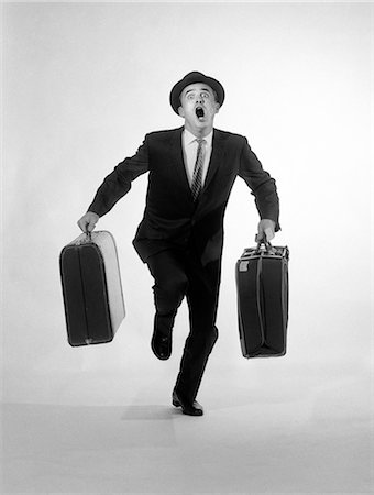 1950s 1960s MAN BUSINESSMAN WORRIED EXPRESSION HAT SUIT TIE CARRYING 2 SUITCASES LUGGAGE RUNNING TO CAMERA CALLING OUT Stock Photo - Rights-Managed, Code: 846-08226155
