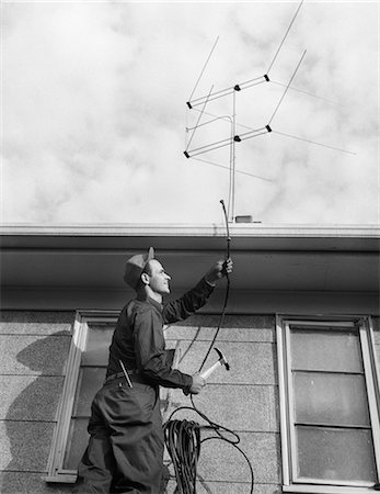 1950s 1960s MAN WORKER ON LADDER RUNNING TELEVISION CABLE TO ANTENNA ON ROOF OF HOUSE Stock Photo - Rights-Managed, Code: 846-08226151