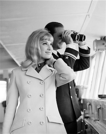 1960s MAN OFFICER IN UNIFORM USING BINOCULARS AND STYLISH BLOND WOMAN STANDING TOGETHER ON BRIDGE OF A CRUISE SHIP Stock Photo - Rights-Managed, Code: 846-08226162