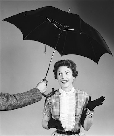 1950s UNSEEN MAN HOLD OUT UMBRELLA TO SMILING WOMAN IN SHIRTWAIST DRESS WHITE RUFFLED BIB FRONT BLACK GLOVES AND CHARM BRACELET Stock Photo - Rights-Managed, Code: 846-08226176
