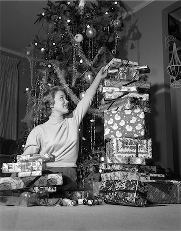 1950s SMILING YOUNG WOMAN SITTING UNDER CHRISTMAS TREE STACKING TALL PILE OF GIFT WRAPPED PRESENTS Stock Photo - Rights-Managed, Code: 846-08226178