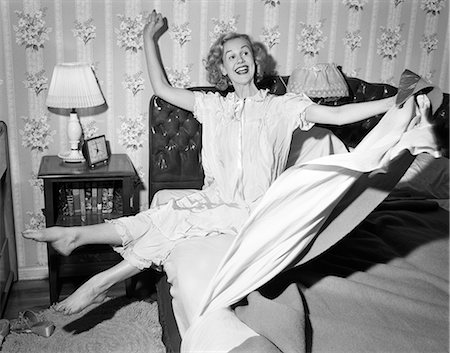 1950s SMILING HAPPY GLEEFUL WOMAN WAKING UP GETTING OUT OF BED FLINGING BACK SHEETS AND BLANKETS Stock Photo - Rights-Managed, Code: 846-08226171
