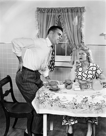 photos of 1940s women in kitchen - 1950s COUPLE AT BREAKFAST TABLE MAN WITH HAND ON HIP SUFFERING BACK PAIN Stock Photo - Rights-Managed, Code: 846-08512674