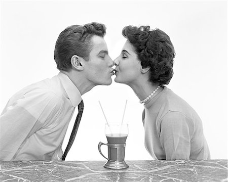 1950s COUPLE MAN WOMAN KISSING PROFILE ROMANCE DATE AT MARBLE COUNTER ONE DRINK MALT SHAKE WITH TWO STRAWS SHARE TEENS TEENAGERS Stock Photo - Rights-Managed, Code: 846-08512687