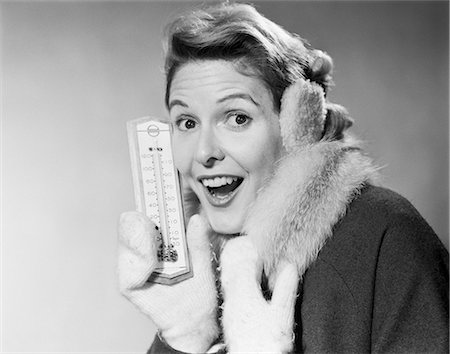 1950s SMILING WOMAN LOOKING AT CAMERA IN WINTER COLD HOLDING THERMOMETER WEARING COAT MITTENS EARMUFFS Stock Photo - Rights-Managed, Code: 846-08512695