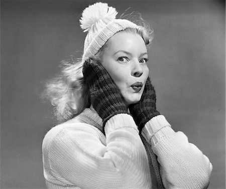 1950s YOUNG WOMAN PURSING LIPS HANDS COVERING EARS LOOKING AT CAMERA WEARING WINTER WOOL SWEATER MITTENS KNIT CAP Stock Photo - Rights-Managed, Code: 846-08512691