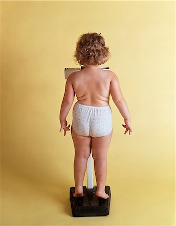 1970s OVERWEIGHT CHUBBY LITTLE GIRL WEIGHING HERSELF ON SCALE BACK VIEW WEARING ONLY PANTIES Stock Photo - Rights-Managed, Code: 846-08512708