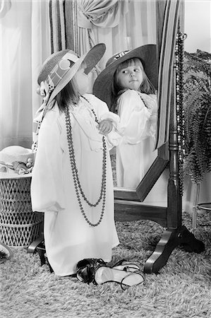 dress up girl - 1980s LITTLE GIRL DRESSED UP IN ADULT CLOTHES POSING BEFORE MIRROR FUN PLAY ROLE PLAYING HAT BEAD NECKLACE Stock Photo - Rights-Managed, Code: 846-08512702