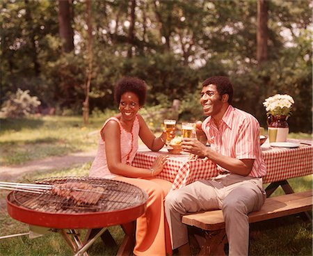1970s SMILING AFRICAN AMERICAN COUPLE MAN WOMAN DRINKING BEER AT BACKYARD BARBECUE Stock Photo - Rights-Managed, Code: 846-08512712