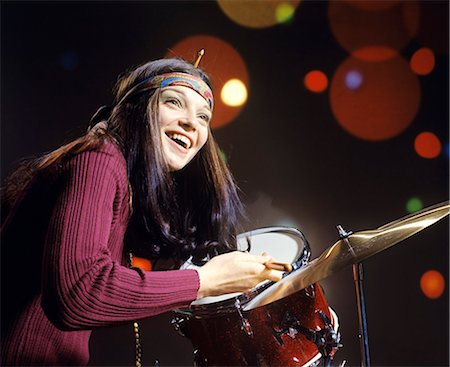 fun happy colorful background images - 1970s SMILING YOUNG WOMAN WEARING HEADBAND PLAYING DRUMS Stock Photo - Rights-Managed, Code: 846-08512721