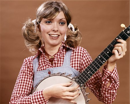 1970s YOUNG WOMAN IN CHECKED SHIRT AND OVERALLS WITH HAIR IN PONYTAILS PLAYING BANJO Stock Photo - Rights-Managed, Code: 846-08512722