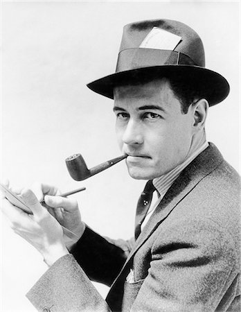 1930s 1940s MAN REPORTER WEARING HAT WITH PRESS PASS WRITING NOTES IN PAD TABLET SMOKING PIPE LOOKING AT CAMERA Stock Photo - Rights-Managed, Code: 846-08512746