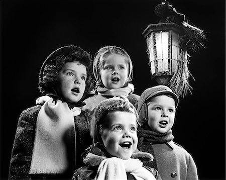 1950s FOUR YOUNG CHILDREN SINGING CHRISTMAS CAROLS OUTDOOR BY LANTERN LIGHT Stock Photo - Rights-Managed, Code: 846-08512756